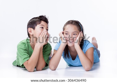 Boy whispers to sister. - stock photo