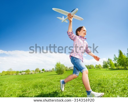 Boy who is holding airplane toy during running in the green meadow during summer day in the park - stock photo