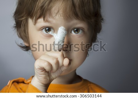 boy with a bandaged wound on his finger (focus on finger) - stock photo