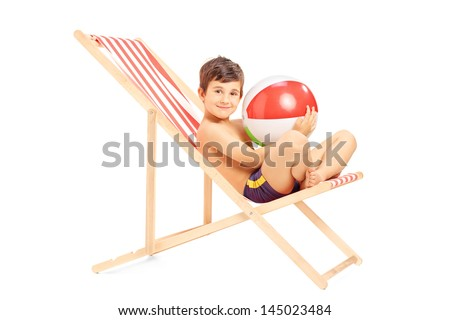 Boy with a beach ball sitting on an outdoor chair isolated on white background - stock photo