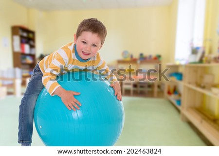 boy with a big ball on the background of the nursery.passionate child for interesting occupation,active lifestyle,happiness concept,carefree childhood concept. - stock photo
