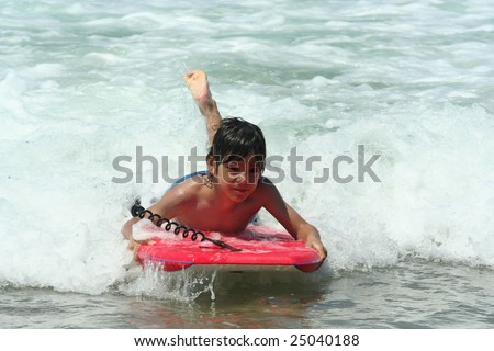 boy with a bodyboard on the beach