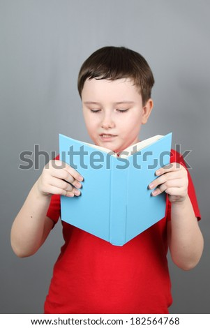 Boy with a book on a gray background. - stock photo