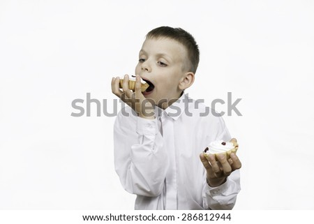 Boy with a cream cake in the hands on a white background. - stock photo