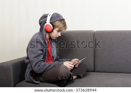 Boy with a digital tablet sitting on the couch - stock photo