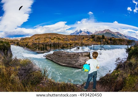 Boy with a globe under his arm on the shore of the waterfall. Chile, Patagonia, Paine Cascades. Torres del Paine National Park - Biosphere Reserve