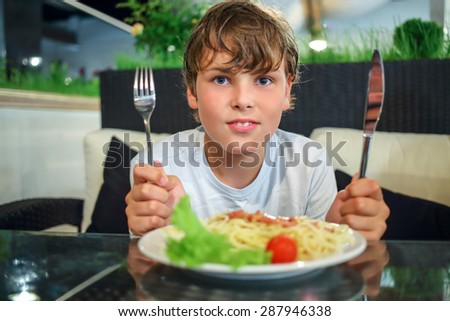 boy with a knife and fork in front of a plate of pasta - stock photo