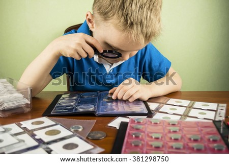 boy with a magnifying glass is considering the old coin numismatist