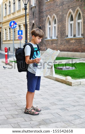 Boy with a map on the city street