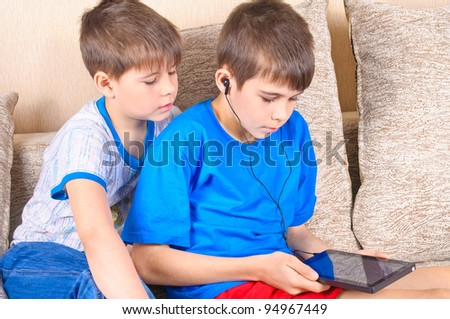 Boy with a Tablet PC. The boy on the couch playing with the tablet - stock photo