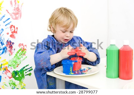 Boy with an apron playing with various colors finger paint
