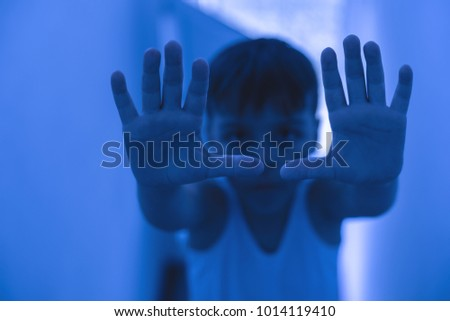 boy with an outstretched arm in a room with fluorescent light
