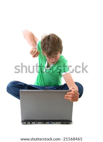 boy with angry expression in front of computer - stock photo