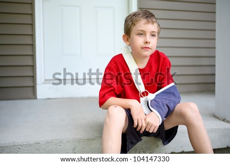 Boy with arm in a sling sitting on a porch - stock photo