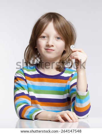 Boy with Blond Hair Holding up a Coin  - stock photo