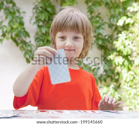 Boy with Blond Hair Playing Cards Outdoors - stock photo