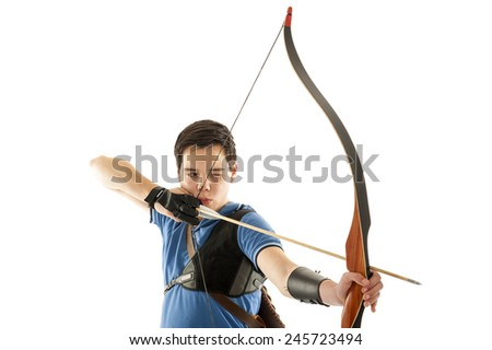 Boy with blue shirt aiming with bow and arrow - stock photo