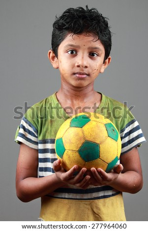 Boy with body smeared with mud holds a football  - stock photo