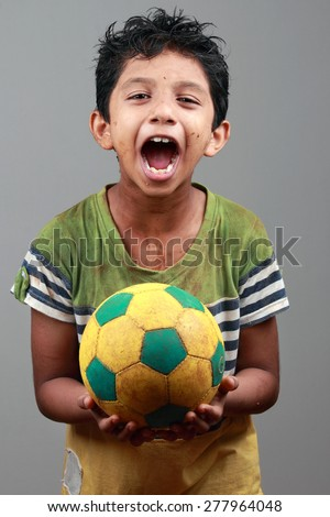 Boy with body smeared with mud holds a football and shows energy - stock photo