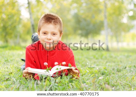 Boy with book wearing red sweater laying on grass
