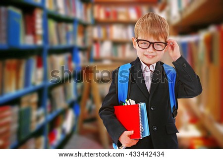 Boy with books in school library - stock photo