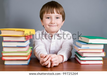 Boy with books on a gray background - stock photo