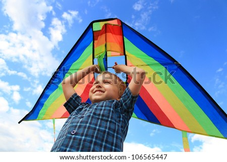 Boy with bright kite over the head on the blue sky view
