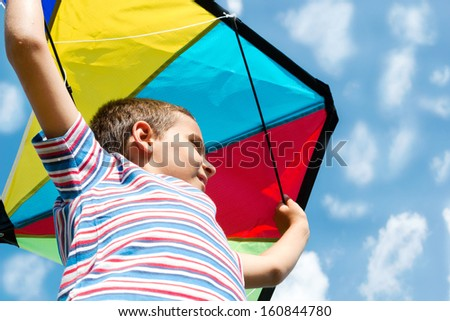 Boy with bright kite over the head on the blue sky view  - stock photo