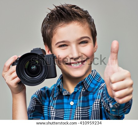 Boy with camera taking pictures. Happy fun boy  with dslr camera showing the thumb up - stock photo
