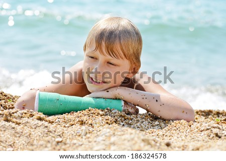 boy with cast on hand laying on the beach