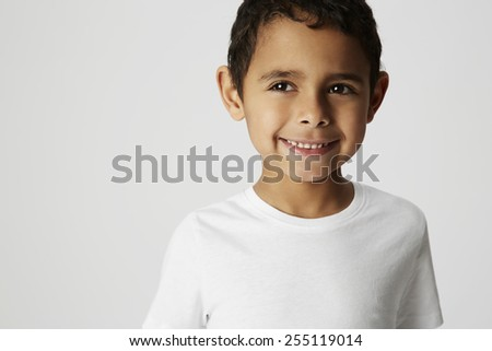 Boy with cheeky grin in studio - stock photo
