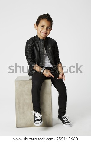 Boy with cheeky smile in leather jacket sitting in studio - stock photo