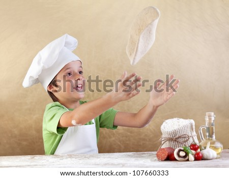 Boy with chef hat preparing the pizza dough - kneading and stretching