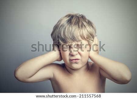 boy with closed ears on a gray background - stock photo