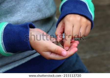 Boy with Coins, A young boy counting his savings or pocket money. - stock photo