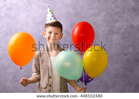 Boy with color balloons on grey background