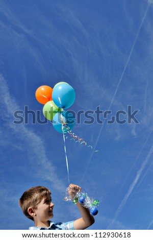 boy with colorful balloons over bright sky background