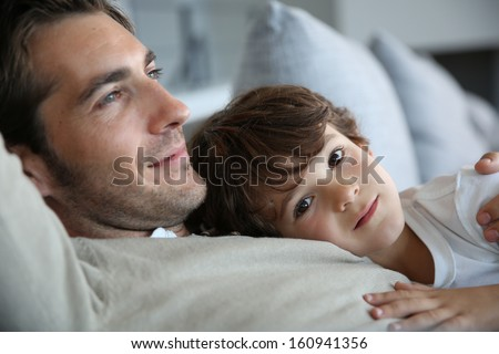 Boy with daddy relaxing on his chest