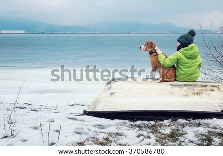 Boy with dog sitting together on the old boat near winter lake - stock photo