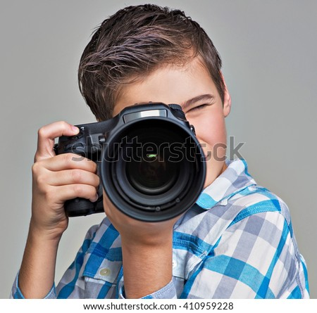Boy  with dslr camera photographing.  Teen  boy with camera taking pictures. - stock photo