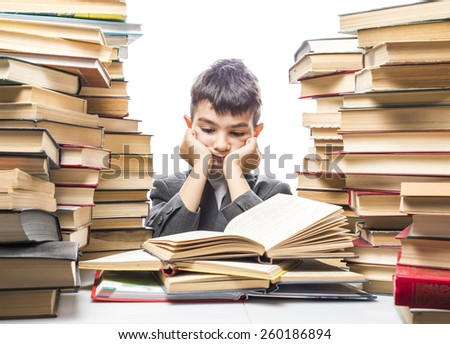 boy with enthusiasm reads the book in a vast body of literature - stock photo