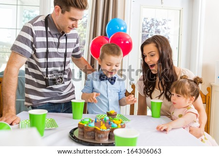 Boy with family celebrating birthday party at home