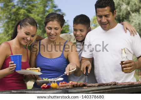 Boy with family gathered around the grill at picnic - stock photo