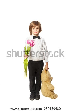 Boy with flowers and a teddy bear standing on a white background in a shirt