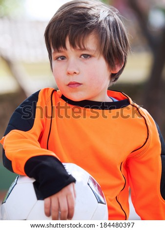 Boy with football soccer / shirt and ball in a park
