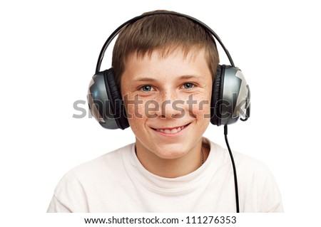 boy with freckles is listening to music on headphones