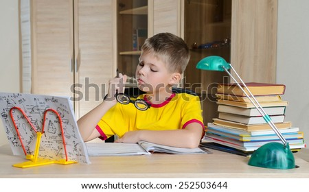 Boy With Funny Glasses Doing Homework. Child With Learning Difficulties. Boy Having Problems With His Homework. Education Concept. - stock photo