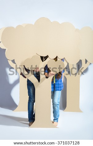 Boy with girl hiding behind cardboard tree and holding a heart. Love concept - stock photo