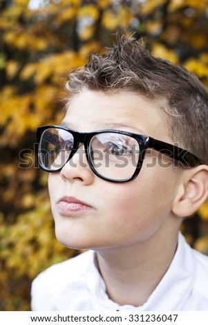 Boy with glasses posing in autumn atmosphere