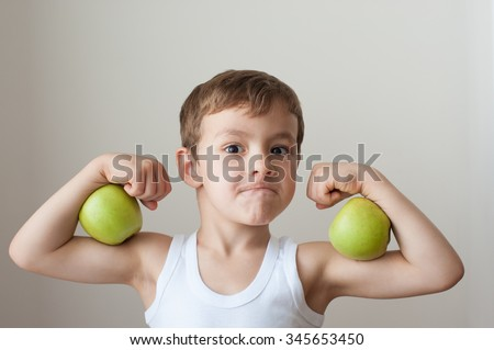 boy with green apples showing biceps - stock photo